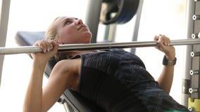 La chica joven atractiva del ajuste levanta para arriba un barbell como exerceise del pecho en el gimnasio metrajes