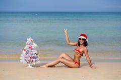 La chica joven atractiva en una playa en el vestido de Papá Noel Fotos de archivo