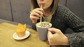 La chica joven atractiva en vidrios bebe el latte del coco del café a través de una paja que se sienta en un café almacen de video