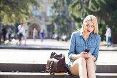 La chica joven atractiva es mensajería a su amigo Foto de archivo libre de regalías