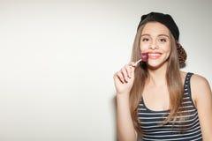 La chica joven atractiva está gozando del caramelo dulce Imagenes de archivo