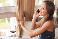 La chica joven atractiva está utilizando el teléfono en café Fotografía de archivo