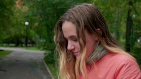 La chica joven atractiva estornuda en un paseo en el parque Slowmo almacen de metraje de vídeo