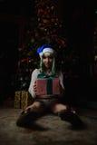 La chica joven atractiva ha recibido el regalo debajo del árbol de navidad Foto de archivo
