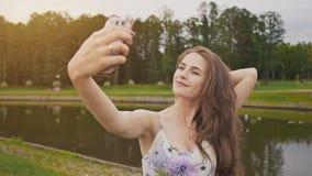 La chica joven atractiva hermosa con el pelo largo y en vestido está haciendo la sesión fotográfica usando smartphone en parque d metrajes