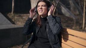 La chica joven atractiva hermosa en chaqueta negra de los vaqueros se está sentando en el banco en parque que disfruta de escucha metrajes