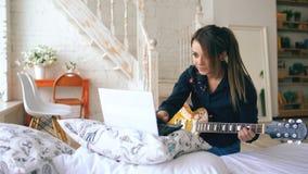 La chica joven atractiva que aprende tocar la guitarra eléctrica con el cuaderno se sienta en cama en dormitorio en casa Foto de archivo libre de regalías