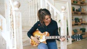 La chica joven atractiva que aprende tocar la guitarra eléctrica se sienta en las escaleras en dormitorio en casa Imagenes de archivo