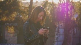 La chica joven atractiva se coloca en centro de la ciudad buzzling ocupada en puesta del sol del verano Mujer joven magnífica en  almacen de video