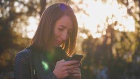 La chica joven atractiva se coloca en centro de la ciudad buzzling ocupada en puesta del sol del verano Mujer joven magnífica en  metrajes