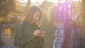 La chica joven atractiva se coloca en centro de la ciudad buzzling ocupada en puesta del sol del verano Mujer joven magnífica en  almacen de metraje de vídeo