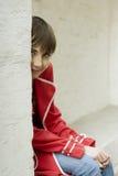 La chica joven atractiva se está sentando cerca de la pared Fotografía de archivo