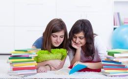 La chica joven ayuda a su aprendizaje del amigo Imágenes de archivo libres de regalías