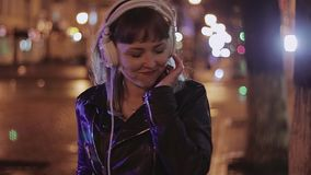 La chica joven baila en la noche en la calle Juegos de la música con los auriculares almacen de video