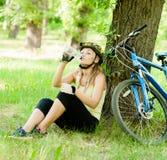 La chica joven bebe el agua de una botella después de biking de la montaña Fotos de archivo libres de regalías