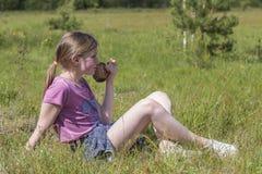 La chica joven bebe el jugo que se sienta en hierba verde Foto de archivo