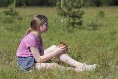 La chica joven bebe el jugo que se sienta en hierba verde Fotografía de archivo libre de regalías