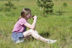La chica joven bebe el jugo que se sienta en hierba verde Fotos de archivo