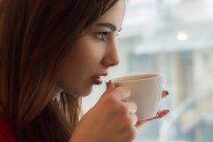 La chica joven bebe té de la taza smal en café Imagen de archivo