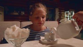 La chica joven bebe té en café por la tarde después de un alza almacen de metraje de vídeo