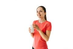 La chica joven bonita bebe después de deportes que entrena y sonríe En un fondo blanco Imagen de archivo