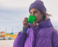 La chica joven bonita bebe el café o el té, calle foto de archivo
