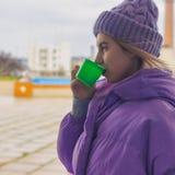 La chica joven bonita bebe el café o el té, calle fotos de archivo libres de regalías