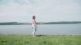 La chica joven bonita camina en una costa costa en día soleado 4K almacen de metraje de vídeo