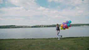 La chica joven bonita corre con los globos a disposición en el coustline 4K metrajes