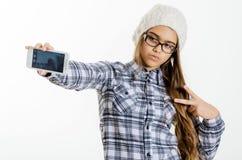 La chica joven bonita de la moda hace el retrato del selfie en smartphone Imagen de archivo