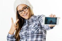 La chica joven bonita de la moda hace el retrato del selfie en smartphone Fotos de archivo libres de regalías