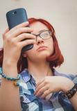 La chica joven bonita de la moda hace el retrato del selfie en smartphone Imágenes de archivo libres de regalías