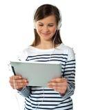 La chica joven bonita disfruta de música que escucha Foto de archivo libre de regalías