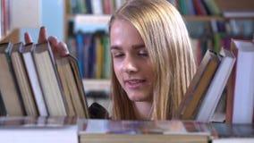 La chica joven bonita elige un libro en la biblioteca almacen de metraje de vídeo