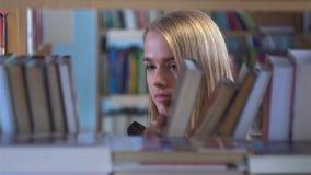 La chica joven bonita elige un libro en la biblioteca almacen de video