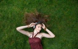 La chica joven bonita escucha música en los auriculares que mienten en hierba Foto de archivo