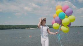 La chica joven bonita mira con los globos a disposición el coustline almacen de video