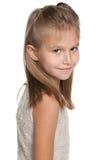 La chica joven bonita mira detrás Fotografía de archivo