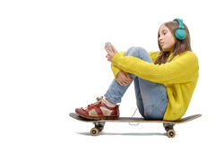 La chica joven bonita que plantea sentarse en patín, escucha música Fotografía de archivo libre de regalías