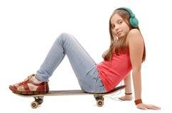 La chica joven bonita que se sienta en el monopatín, escucha una música Imagen de archivo