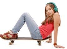 La chica joven bonita que se sienta en el monopatín, escucha una música Imagenes de archivo