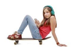 La chica joven bonita que se sienta en patín, escucha música Imágenes de archivo libres de regalías