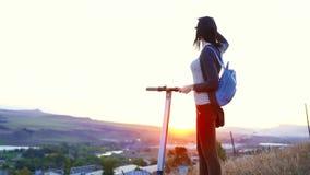 La chica joven camina abajo de la colina con una vespa eléctrica y mira la puesta del sol almacen de metraje de vídeo