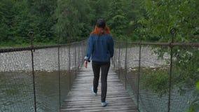 La chica joven camina en puente colgante metrajes