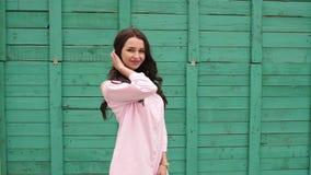 La chica joven camina más allá de una pared de madera verde almacen de video