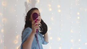 La chica joven canta canciones en un secador y las danzas de pelo que tienen un buen humor Estilo casero almacen de video