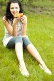 La chica joven come la pizza Fotografía de archivo