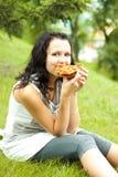 La chica joven come la pizza Foto de archivo libre de regalías