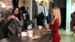 La chica joven compra una falda en una tienda de la moda, ella paga con una tarjeta de crédito plástica metrajes