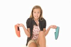 La chica joven con dos zapatos no puede decidir Fotos de archivo